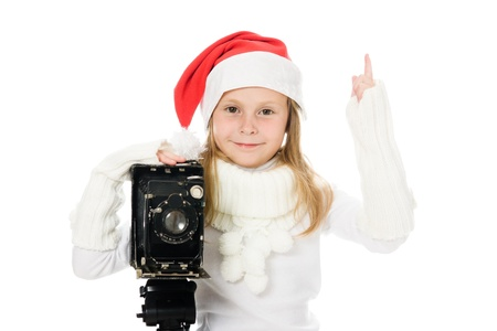 Girl in a Christmas costume with old camera on a white background. photo
