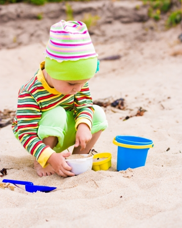 Kid playing on the beach with the childrens shovel and a bucket. photo