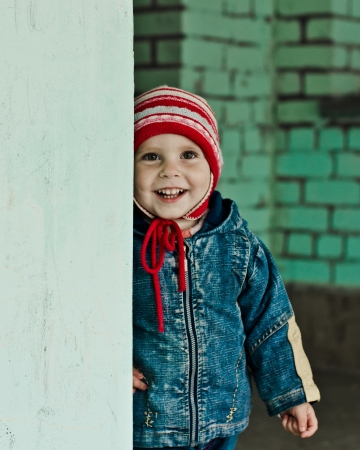 Cheerful baby playing hide and seek in the street. photo