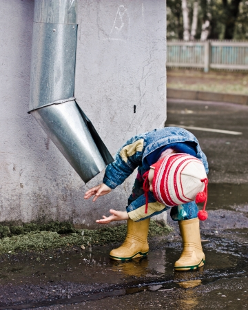 Baby washes up on the street under the drain.