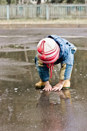 Baby washes up on the road in a muddy puddle.