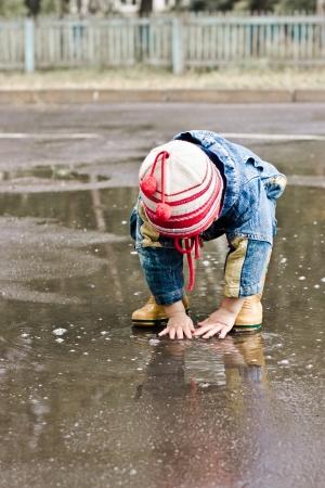 uomo sotto la pioggia: Bambino lava sulla strada in una pozza fangosa.