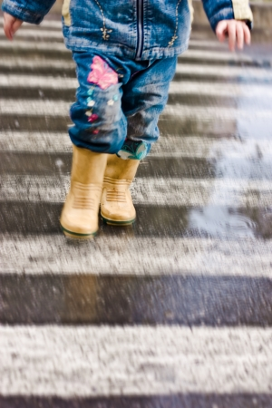 A child runs across the road at a pedestrian crossing.