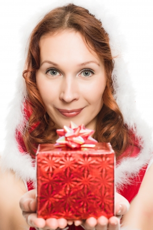 Attractive woman in Christmas dress hands a present, on a white background. photo
