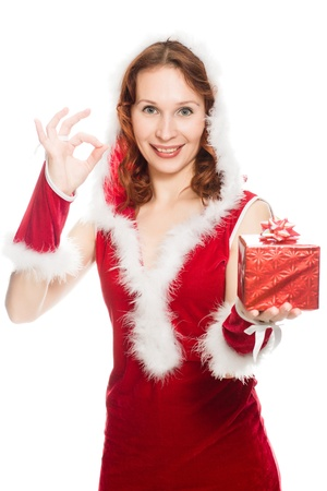 Happy girl in a Christmas dress showing okay sign on a white background. Stock Photo