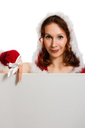 Beautiful woman in Christmas clothing points the finger at clean background. photo