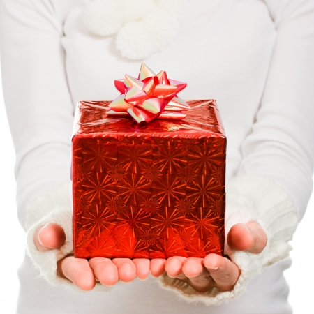 Women's hands hold out a box with a gift on a white background. photo