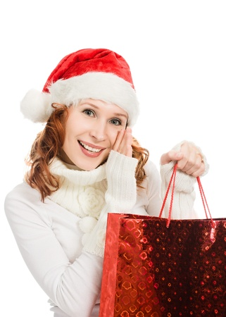 tattle: Beautiful christmas woman in santa hat with a bag in hand, whispering over white background. Stock Photo