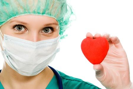 quirurgico: Mujer m�dico con un coraz�n en sus manos sobre un fondo blanco