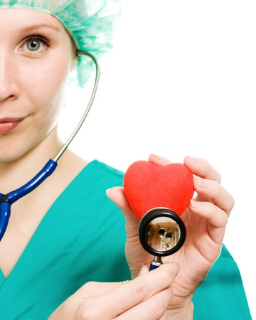 Woman doctor with stethoscope and heart in hands on a white background. Stock Photo