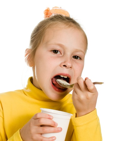 Young girl eating yogurt on a white background. Stock Photo - 15760746