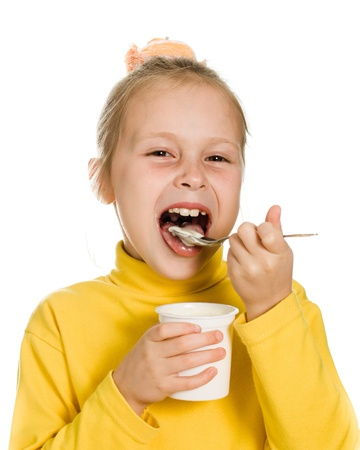 Young girl eating yogurt on a white background. Stock Photo - 15760727