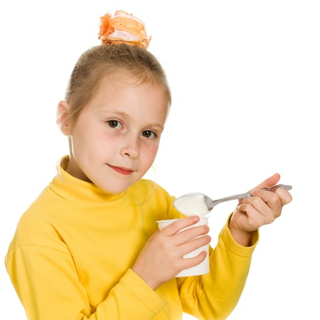 Young girl eating yogurt on a white background. photo