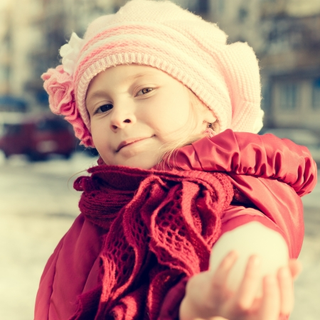 ball lump: A young girl holds out his hand in a snowball on the playground in a retro style. Stock Photo