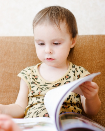 Beautiful cute baby reading a book while sitting on the couch. Stock Photo - 16640101