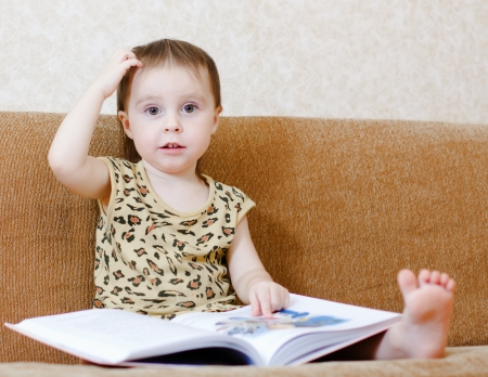 Beautiful cute baby reading a book while sitting on the couch. Stock Photo - 16639981