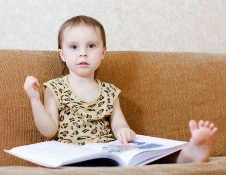 Beautiful cute baby reading a book while sitting on the couch. Stock Photo - 16639996