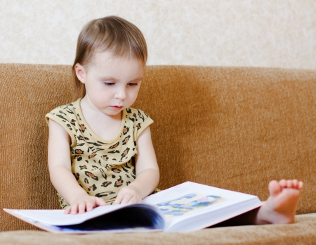 Beautiful cute baby reading a book while sitting on the couch. photo