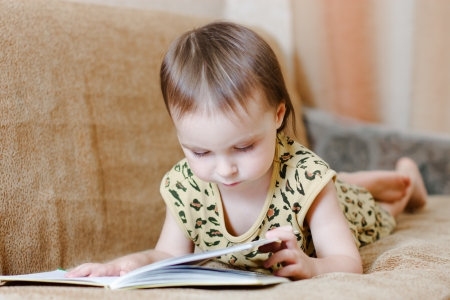 Beautiful cute baby reading a book while lying on the couch. Stock Photo - 16640031