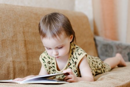 Beautiful cute baby reading a book while lying on the couch. photo