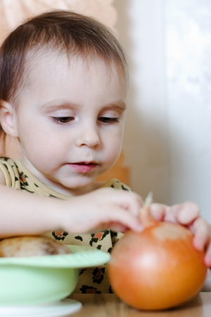 Beautiful cute kid with vegetables in the kitchen. photo