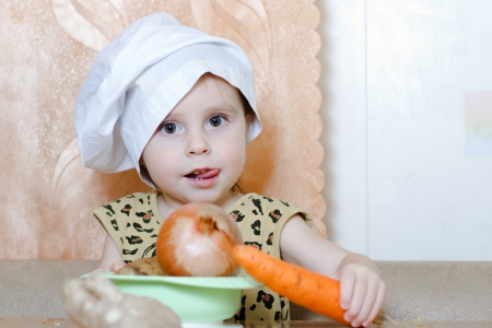 Beautiful cute little cook with vegetables in the kitchen. photo