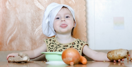 Beautiful cute little cook with vegetables in the kitchen. Stock Photo - 16640185