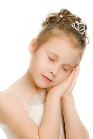 Pretty beautiful girl dreaming with closed eyes on a white background. photo