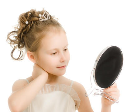 lifestyle looking lovely: Pretty beautiful girl looks in the mirror on a white background. Stock Photo