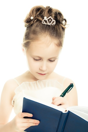 Pretty beautiful girl writing in a notebook on a white background. photo