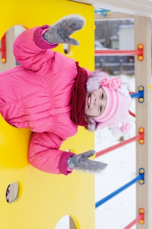 Beautiful happy kid in the red jacket in the winter outdoors. Stock Photo - 16639995