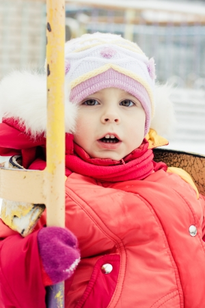 Beautiful happy kid in the red jacket in the winter outdoors. Stock Photo - 16640009