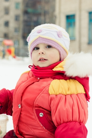 Beautiful happy kid in the red jacket in the winter outdoors. Stock Photo - 16640007