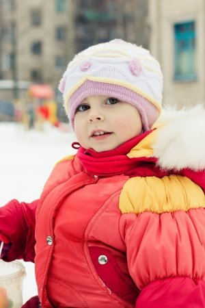 Beautiful happy kid in the red jacket in the winter outdoors. Stock Photo - 16639991