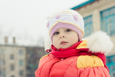 Beautiful happy kid in the red jacket in the winter outdoors. Stock Photo - 16640025