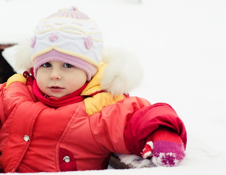 Beautiful happy kid in the red jacket in the winter outdoors. Stock Photo - 16640140