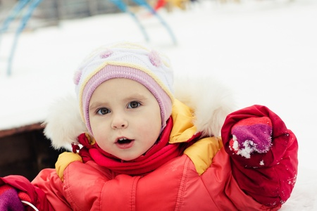 Beautiful happy kid in the red jacket in the winter outdoors. Stock Photo - 16640096