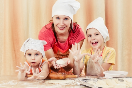 Mother with two daughters, all of the flour with the dough. photo