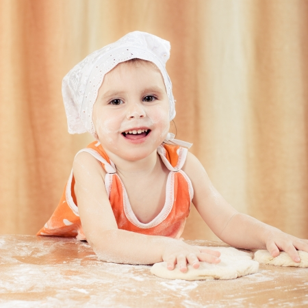 battledore: Pretty beautiful girl covered in flour makes cakes. Stock Photo