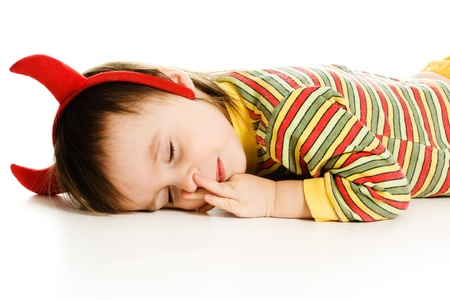 Baby with horns imp sleeps on the floor on a white background. photo