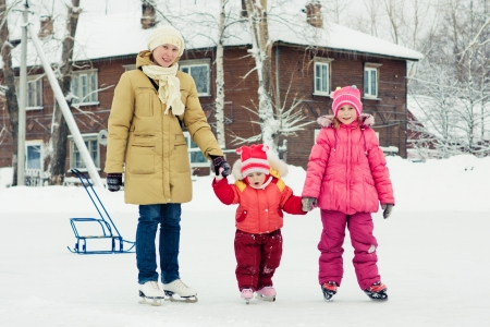 Mother with her daughters skates on ice skating in the winter. photo