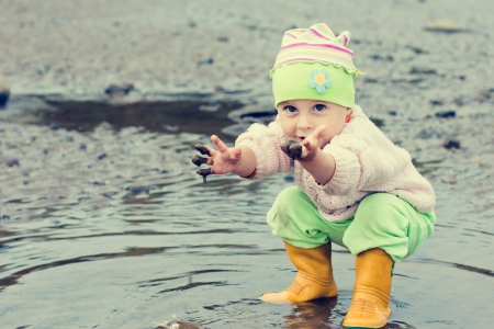Baby washes up in a muddy puddle.