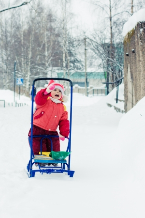 Kid rolls sleigh in winter on snow. photo
