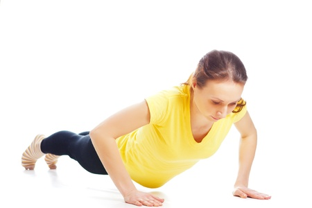 Young woman doing yoga exercise on a white background. photo