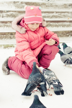 Child feeding doves in the city street winter. photo