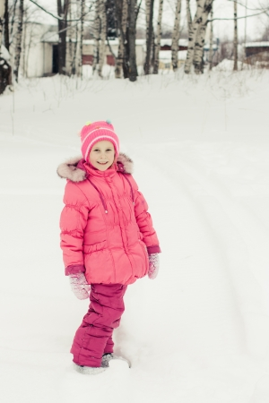 Beautiful happy girl in the red jacket winter outdoors. photo