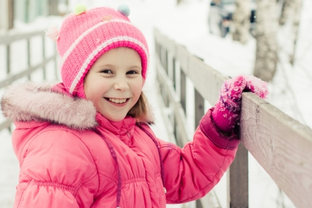 handrails: Beautiful happy kid on the bridge holding the handrails in the winter outdoors. Stock Photo