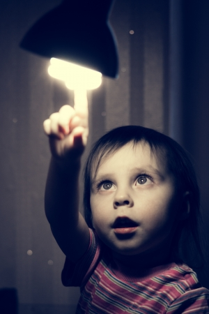 Little child points his finger at a lighted lamp. photo