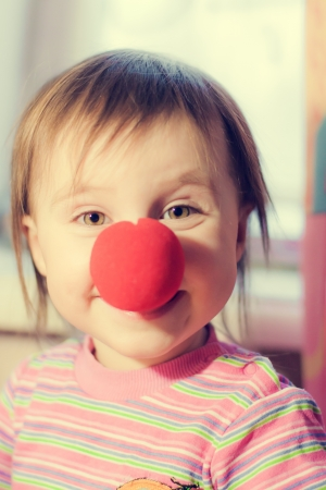 Kid with red nose clown fooling around. photo