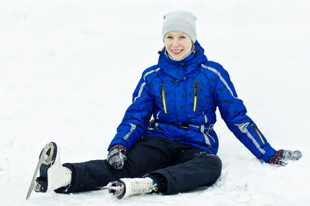 Woman in skates sitting on the ice smiling. photo